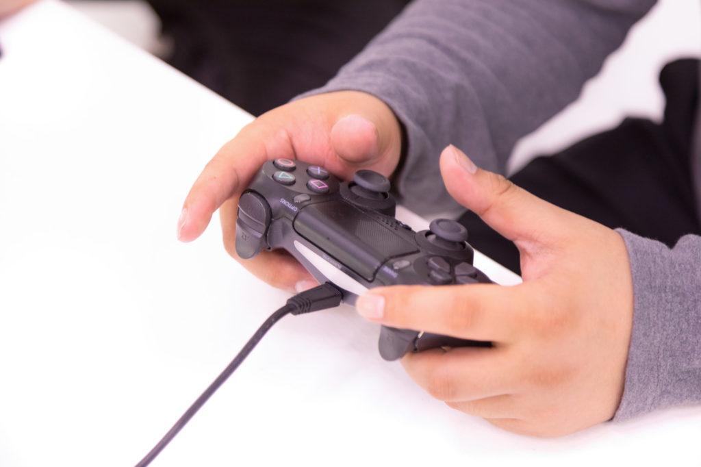 コントローラを持ちながらテレビゲームしているプレイヤー
